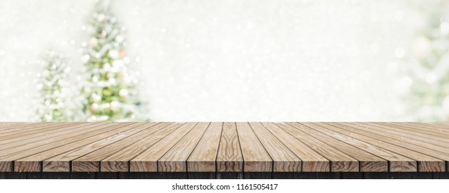 Christmas background banner.wooden table at snow falling winter montage with abstract pale blur christmas tree with white bokeh light,Holiday rustic tabletop backdrop,Mock up shelf for product display