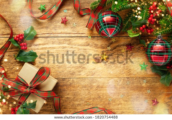 Christmas background with Christmas baubles, branches of holly and fir on wooden background. Winter festive concept. Flat lay, copy space.