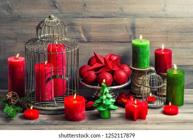 Christmas background with birdcage, burning candles and baubles decoration. Vintage toned picture