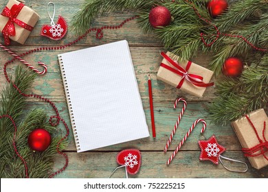 Christmas background with blank notebook, fir branches, decorations and  gift boxes. Space for text. Top view. Christmas to-do list or wish list.