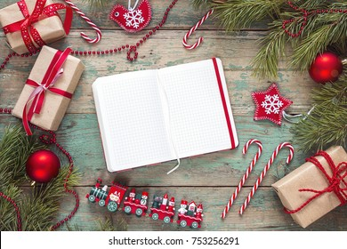 Christmas background with blank notebook, fir branches, decorations and gift boxes on wooden table. Space for text. Top view. Christmas to-do list or wish list.