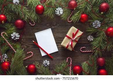 Christmas background with blank notebook, fir branches, decorations and  gift box. Space for text. Top view. Christmas to-do list or wish list.