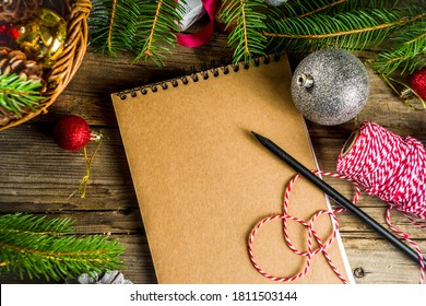 Christmas background with blank notebook for to-do list or wish list. with christmas fir branches, decorations and gift boxes. Wooden rustic background copy space
