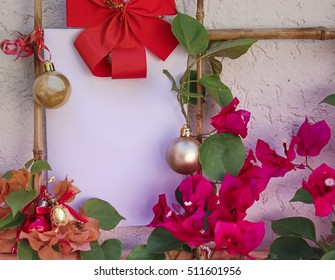 Christmas background with blank white greeting card for invitation letter or inbound email marketing. Surrounded by holiday decorations and real red and gold flowers. Sustainable concept image.