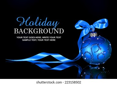 Christmas background with a blue ornament and ribbon on a black background
