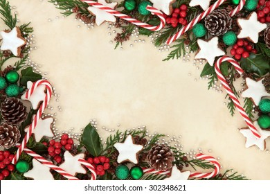 Christmas background border of gingerbread biscuits,  candy canes, bauble decorations, holly and winter greenery over old parchment paper.