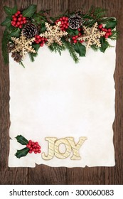 Christmas background border with gold joy sign and snowflake bauble decorations, holly, ivy and winter greenery on parchment paper over old oak wood.