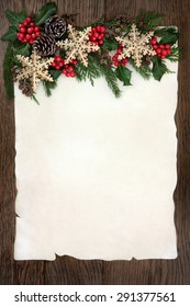 Christmas background border with gold snowflake bauble decorations, holly, ivy, cedar cypress and fir on parchment paper over old oak wood.
