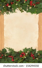 Christmas background border with holly, ivy and mistletoe on old parchment paper over oak.