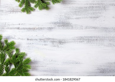 Christmas background. Branches of a Christmas tree in the corner of the background and from above. White wooden background. Place for text