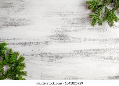 Christmas background. Branches of a Christmas tree in the corners of the background. White wooden background. Place for text