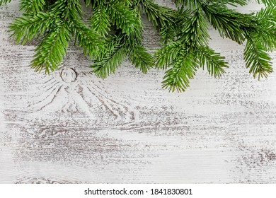 Christmas background. Branches of a Christmas tree at the top of a white wooden background. Place for text