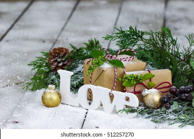 Christmas background with brown paper packages, the word Love and Christmas ornaments by green Christmas tree garland surrounded by snow background; Christmas background with white copy space