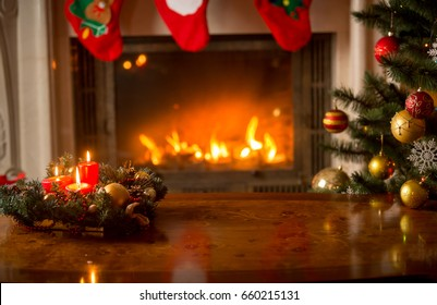 Christmas background with burning candles on wooden table in front of fireplace and Christmas tree