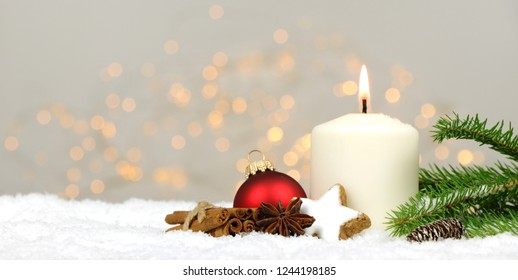 Christmas background - candle with christmas balls pine branches and spices in the snow with blurred lights in the background