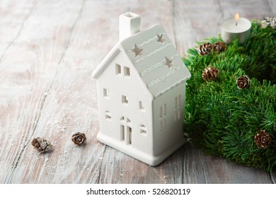 Christmas background with candle house and holiday Xmas decorations on white rustic wooden background. Top view. Winter time concept