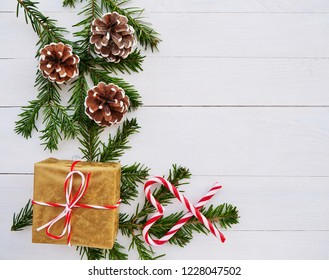 Christmas background with candy cane, gift, cones and fir branches over white wooden background.