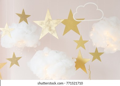 Christmas background. Christmas card. Clouds made of cotton with light, hanging by a thread. Star gold color. Cozy photo zone for a photo shoot. Children's room decoration.