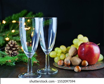 Christmas background with champagne glasses. Christmas lights, pine and decorations and fruits on the table over black background.