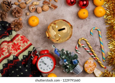 Christmas background with a clock and a golden piggy bank, sweets, Christmas balls and tangerines. Cozy still life with a sweater. Place under your text.