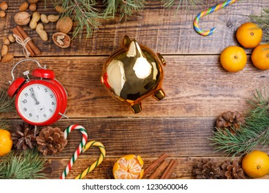 Christmas background with a clock and a golden piggy bank, sweets, Christmas balls and tangerines.