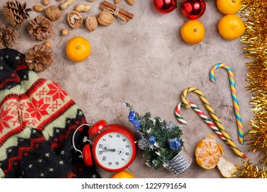 Christmas background background with a clock, sweets, Christmas balls and tangerines. Cozy still life with a sweater.