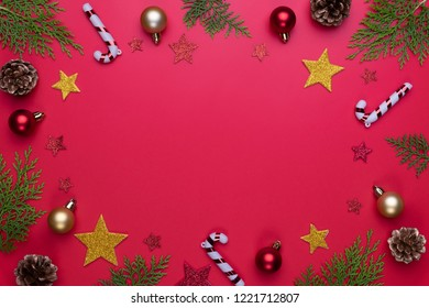 Christmas background concept. Top view of Christmas gift box with spruce branches, pine cones, red berries and bell on red background.