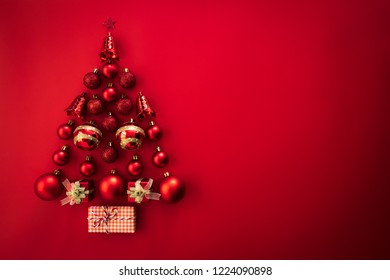 Christmas background concept. Top view of gift box with red ball and bell in shape of Christmas tree on red background.