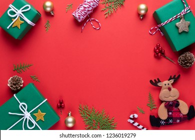 Christmas background concept. Top view of Christmas green gift box red sock with spruce branches, pine cones, red berries and bell on red background.