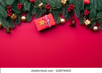 Christmas background concept. Top view of Christmas gift box red balls with spruce branches, pine cones, red berries and bell on red background.