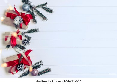 Christmas background concept. Top view of Christmas gift box with spruce branches, pine cones, red berries on white wooden table background.