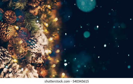 Christmas background. Cones and a garland on a dark blue background.