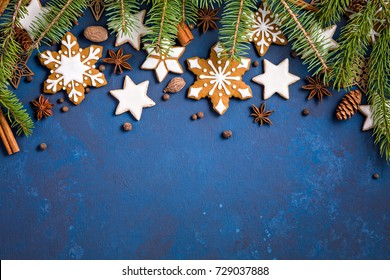Christmas background with cookies, fir branches and spices on dark blue.