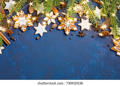 Christmas background with cookies, fir branches, lights, and spices on dark blue.