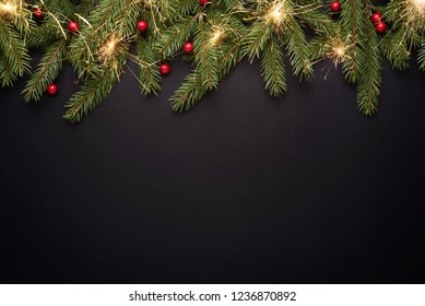 Christmas background with copy space for advertising text. Fir branches and holly berries on black. Flat lay, top view
