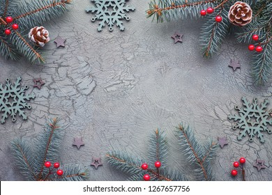 Christmas background with copy-space. Flat lay with decorated fir twigs on dark textured background in green and red