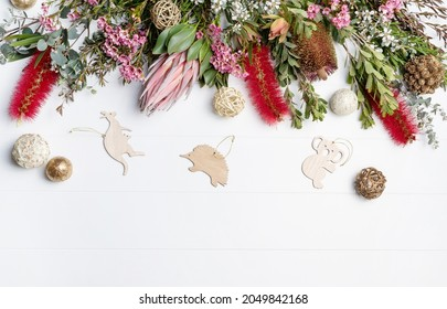 Christmas Background decorated with Australian native wooden animals and flowers - Eucalyptus leaves, Protea, Banksia, Callistemon, Tea Tree and Wax-flowers, on a rustic white background.