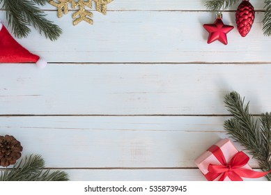 Christmas background decoration frame with gift boxes, red ornaments and fir branches flat lay with copy space on vintage wooden table