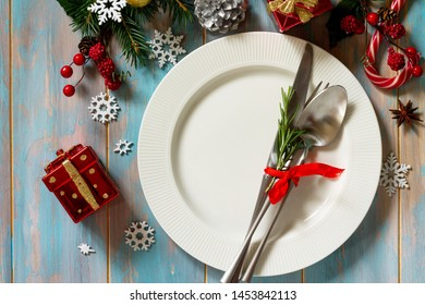 Christmas background. Christmas decoration table. Festive white plate and cutlery with Christmas decor on retro wooden table. Top view flat lay.