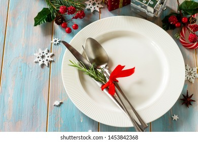 Christmas background. Christmas decoration table. Festive white plate and cutlery with Christmas decor on retro wooden table. Free space for your text.