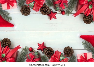 Christmas background decorations frame with gift boxes, red ornaments and fir tree flat lay with copy space on vintage wooden table, Greeting card for merry xmas and happy new year holiday seasonal