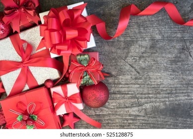 Christmas background decorations with gift boxes and red ribbon bow on wooden table with copy space flat lay style, Greeting invitation card for new year seasonal