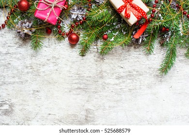 christmas background with decorations and gift boxes covered with snow on white wooden background with copy space