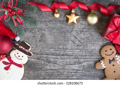 Christmas background decorations with gift boxes, snowman, gingerbread man cookies and red ribbon bow with ornaments bauble on wooden table flat lay with copy space, Greeting card for new year