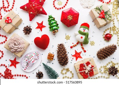 Christmas background with decorations. New Year symbol - decorative fir tree. Gifts in craft paper, pine cones, red hearts and confetti. Flay lay, top view.