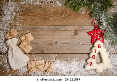 Christmas background with decorations, parcels and card tor you text on wooden board