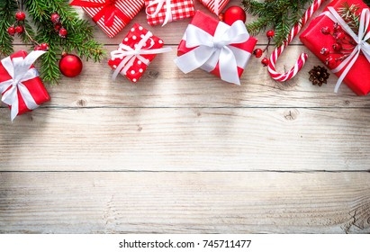 Christmas background with decorations and red gift boxes on wooden board with copy space