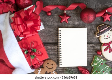 Christmas background decorations with red ribbon bow and ornaments and open notebook on wooden table top view