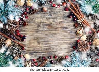 Christmas background with festive decorations, winter spices,  cranberries, nuts and blue fir branches, top view, copy space