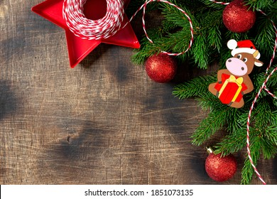 Christmas background with fir branches decorated with the symbol of 2021 bull cow. Christmas background. Red ornaments on spruce branches. Christmas Flatlay. Top view from copyspace